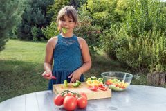 Cute little girl is tasting green pepper. While cooking salad from fresh vegetables outdoors Royalty Free Stock Photo