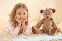 Cute little girl with teddy bear reading book. At home Royalty Free Stock Images