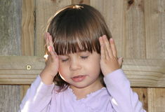 Cute Little Girl Thinking. A cute little toddler with her hands to her head and her eyes closed, thinking stock photos