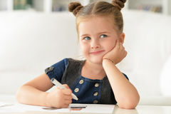 Cute little girl thinking about something. Writing notes royalty free stock image
