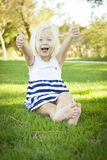 Cute Little Girl with Thumbs Up in the Grass Stock Image