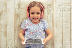 Cute little girl. Top view of cute little girl in headphones listening to music using a tablet, looking at camera and smiling while lying on wooden floor royalty free stock photography