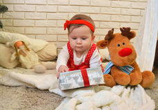 Cute little girl and toy deer under the Christmas tree. Baby holding a gift in her hands Royalty Free Stock Photo
