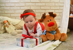 Cute little girl and toy deer under the Christmas tree. Baby holding a gift in her hands Stock Photography