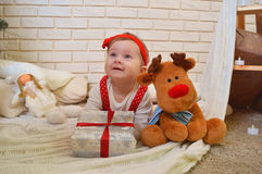 Cute little girl and toy deer under the Christmas tree. Baby holding a gift in her hands and smiling Stock Image