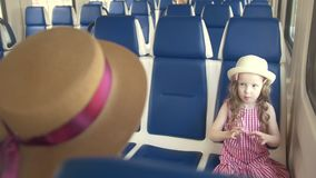 Cute little girl traveling in empty train with her mom - sends an air kiss. Close up stock video footage
