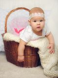 Cute little girl try to get out of basket Stock Photos