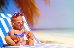 Cute little girl trying on sunglasses at the beach Royalty Free Stock Images