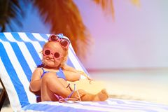 Cute little girl trying on sunglasses at the beach Stock Photography