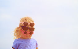 Cute little girl trying on sunglasses at sky Stock Photos