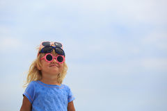 Cute little girl trying on sunglasses at sky Stock Image