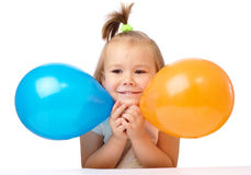 Cute little girl with two colored balloons Stock Photography