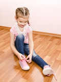 Cute little girl tying her shoes Royalty Free Stock Photos