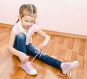 Cute little girl tying her shoes Royalty Free Stock Images