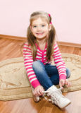 Cute little girl tying her white shoes at home Royalty Free Stock Image