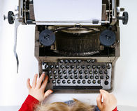 Cute little girl typing on vintage typewriter keyboard Royalty Free Stock Images