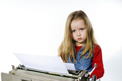 Cute little girl typing on vintage typewriter keyboard Royalty Free Stock Photo
