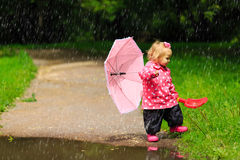 Cute little girl with umbrella in raincoat and boots Royalty Free Stock Images