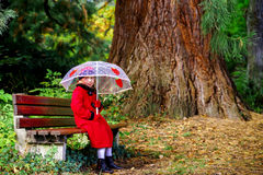 Cute little girl with umbrella sitting under the big pinetree Royalty Free Stock Images