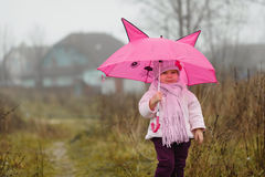 The cute little girl under an pink umbrella in the fall in autum Stock Photos