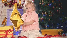 Cute little girl unpacking gift box, near decorated Christmas tree. Presents! Kid opens Christmas gifts, boxes. New Year 2017 stock video footage