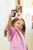 Cute little girl using cell phone taking a selfie Royalty Free Stock Photos
