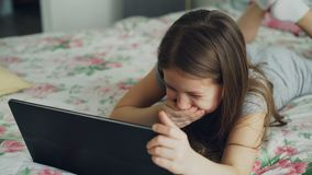 Closeup of cute little girl using digital tablet and smiling while lying in bed. Child wathcing cartoon movie on. Cute little girl using digital tablet and stock video footage