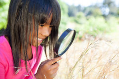 Cute little girl using magnifying glass in park Royalty Free Stock Photography
