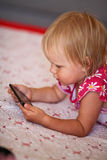 Cute Little girl using mobile phone Royalty Free Stock Images