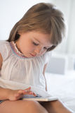Cute Little girl using mobile phone at home Stock Image