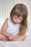 Cute Little girl using mobile phone at home Stock Photo