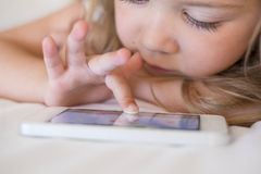 Cute Little girl using mobile phone at home Royalty Free Stock Photos