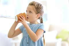 Cute little girl using plastic cup as telephone  while playing at home Royalty Free Stock Photos
