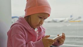 Cute little girl using smart phone in airport, close-up. Portrait cute little girl using smart phone in airport, close-up. Seriously child in warm clothes sits Royalty Free Stock Images