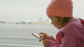 Cute little girl using smart phone in airport, close-up. Portrait cute little girl using smart phone in airport, close-up. Seriously child in warm clothes sits Royalty Free Stock Photography