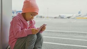 Cute little girl using smart phone in airport, close-up. Portrait cute little girl using smart phone in airport, close-up. Seriously child in warm clothes sits Stock Photo