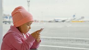 Cute little girl using smart phone in airport, close-up. Portrait cute little girl using smart phone in airport, close-up. Seriously child in warm clothes sits Stock Image