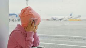 Cute little girl using smart phone in airport, close-up. Portrait cute little girl using smart phone in airport, close-up. Seriously child in warm clothes sits Royalty Free Stock Photos