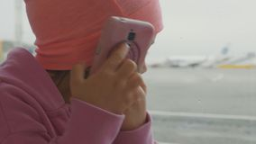Cute little girl using smart phone in airport, close-up slow motion. Portrait cute little girl using smart phone in airport, close-up slow motion. Seriously stock footage