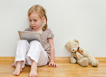 Cute little girl using tablet computer Royalty Free Stock Image