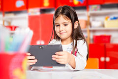 Cute little girl using tablet computer Royalty Free Stock Photo