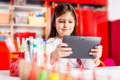 Cute little girl using tablet computer Royalty Free Stock Photography