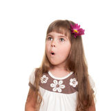 Cute little girl very surprised and looking up somewhere. With bud of chrysanthemum in hair against white background Royalty Free Stock Photography