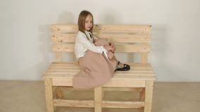 Cute girl in a blouse and black hat, she poses in the Studio with a white wall. Cute little girl in vintage clothes sitting on a wooden eco-bench in a white stock footage
