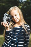 Cute little girl with a vintage rangefinder camera. Beautiful long blond hair Royalty Free Stock Images