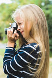 Cute little girl with a vintage rangefinder camera. Beautiful long blond hair Stock Photos