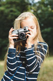 Cute little girl with a vintage rangefinder camera. Beautiful long blond hair Stock Photo