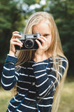 Cute little girl with a vintage rangefinder camera. Beautiful long blond hair Royalty Free Stock Photography