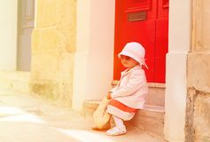 Cute little girl waiting at the door on street of Stock Photography