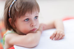 Cute little girl waiting for someone or something. Cule little girl looking for someone or something at coffe table. Closeup portrait with shallow depth of field Stock Photography